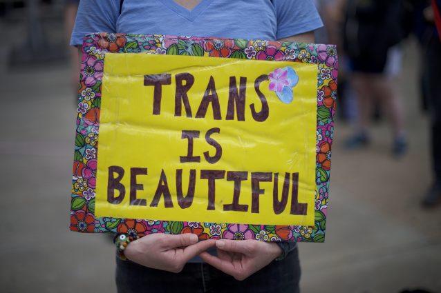 Un'attivista trans con un cartello