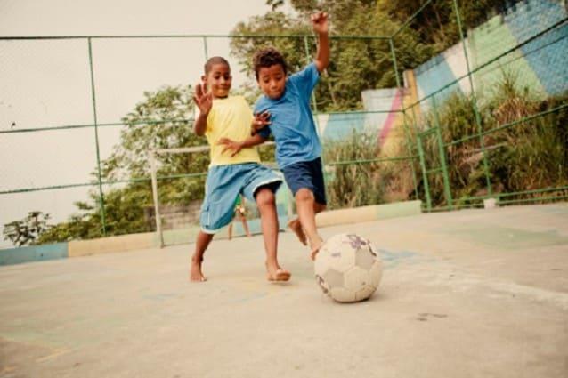 Bambini giocano a pallone in una favela brasiliana