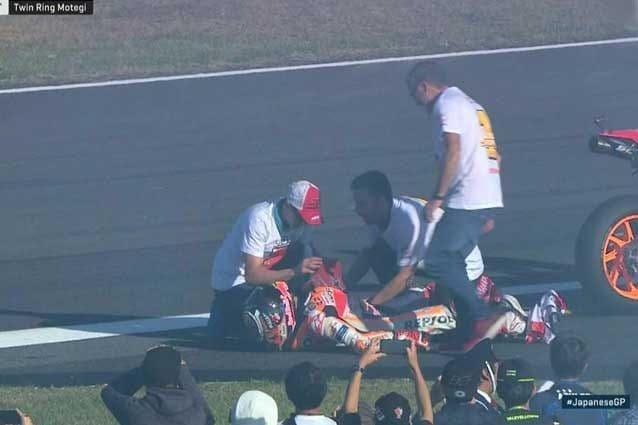 Marc Marquez a terra mentre il fratello Alex gli rimette la spalla in sede / MotoGP.com