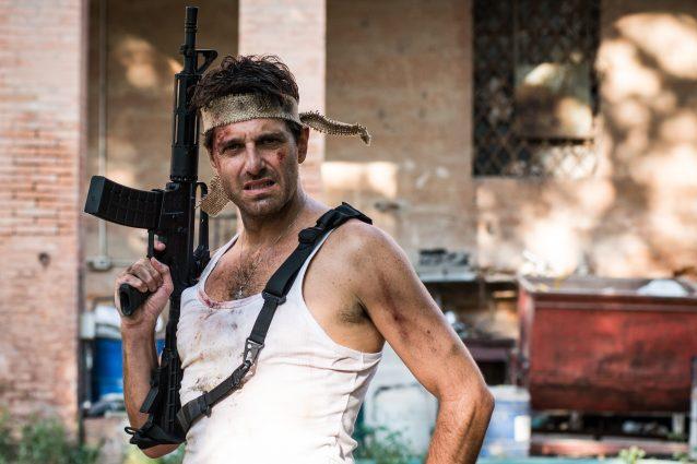 """Morelli che imbraccia un mitra, ha il volto insanguinato e l'espressione alla John Rambo. Praticamente: il manifesto de """"L'Ispettore Coliandro""""."""