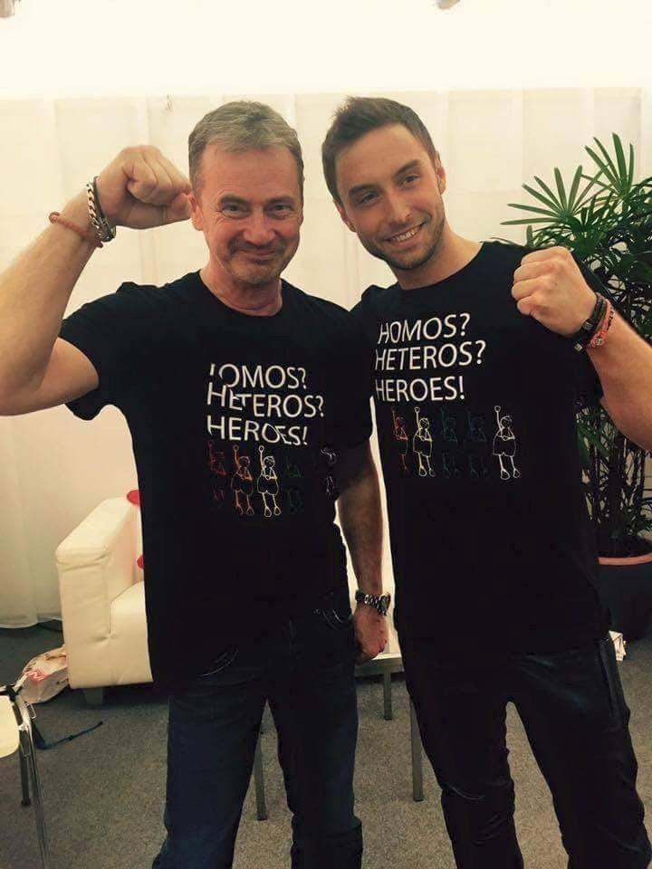 """Mans Zelmerlow e Christer Bjorkman (""""show producer"""" dell'Eurovision 2013 e """"supervisor"""" del Melodifestivalen) indossano una maglia contro le discriminazioni. """"Homos? Heteros? Heroes""""."""