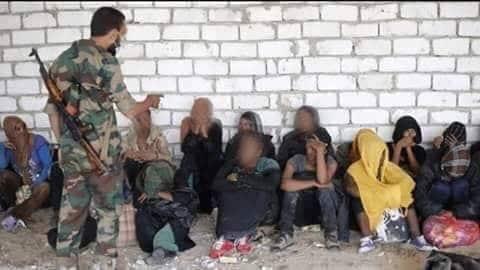 Un militare libico si rivolge minaccioso verso un gruppo di detenuti nel centro di Kesher bin al Kesher, a sud di Tripoli