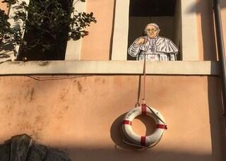 Aprite i porti, Papa Francesco offre un salvagente ai migranti: il murales di Maupal apparso a Roma