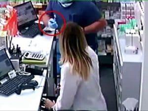 Il rapinatore mentre minaccia il personale con un taglierino