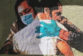 Un murales allo Spallanzani: l'abbraccio che le vittime non hanno potuto dare ai loro cari
