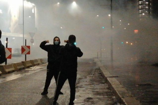 Durante la violenta protesta a Milano, mentre la polizia lanciava i lacrimogeni, un contestatore si è messo in posa per una foto