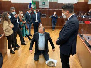 Il consigliere Michele Usuelli in ginocchio nell'aula del Consiglio regionale (Foto MiaNews)