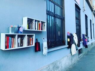 Milano, inaugurato il Muro della Gentilezza: vestiti, giubbotti e libri appesi per chi ne ha bisogno