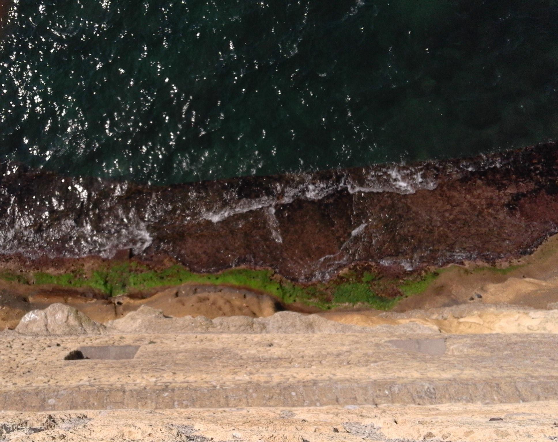 Qui l'incessante e plurisecolare lavorio del mare sulla roccia di tufo che regge il Castel dell'ovo (@Fanpage.it by CC 3.0).