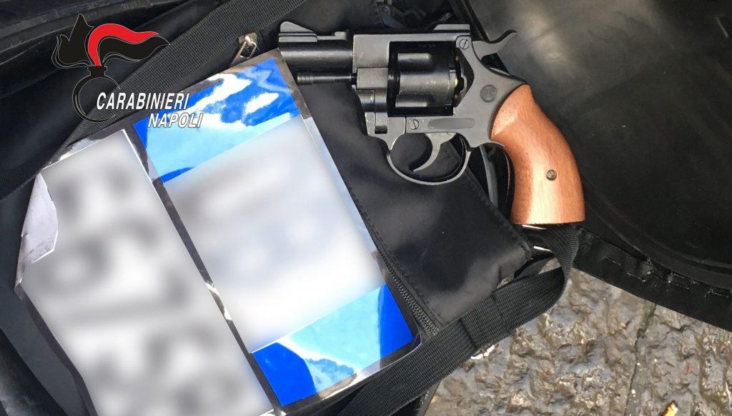 La pistola a salve priva del tappo rosso e l'adesivo con la targa di una motocicletta recuperati dai carabinieri.