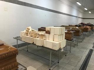 Casse di legno con feti ed arti umani accatastate nel deposito del cimitero di Poggioreale