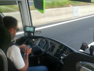 Il conducente del bus Flixbus guarda il cellulare mentre guida in autostrada