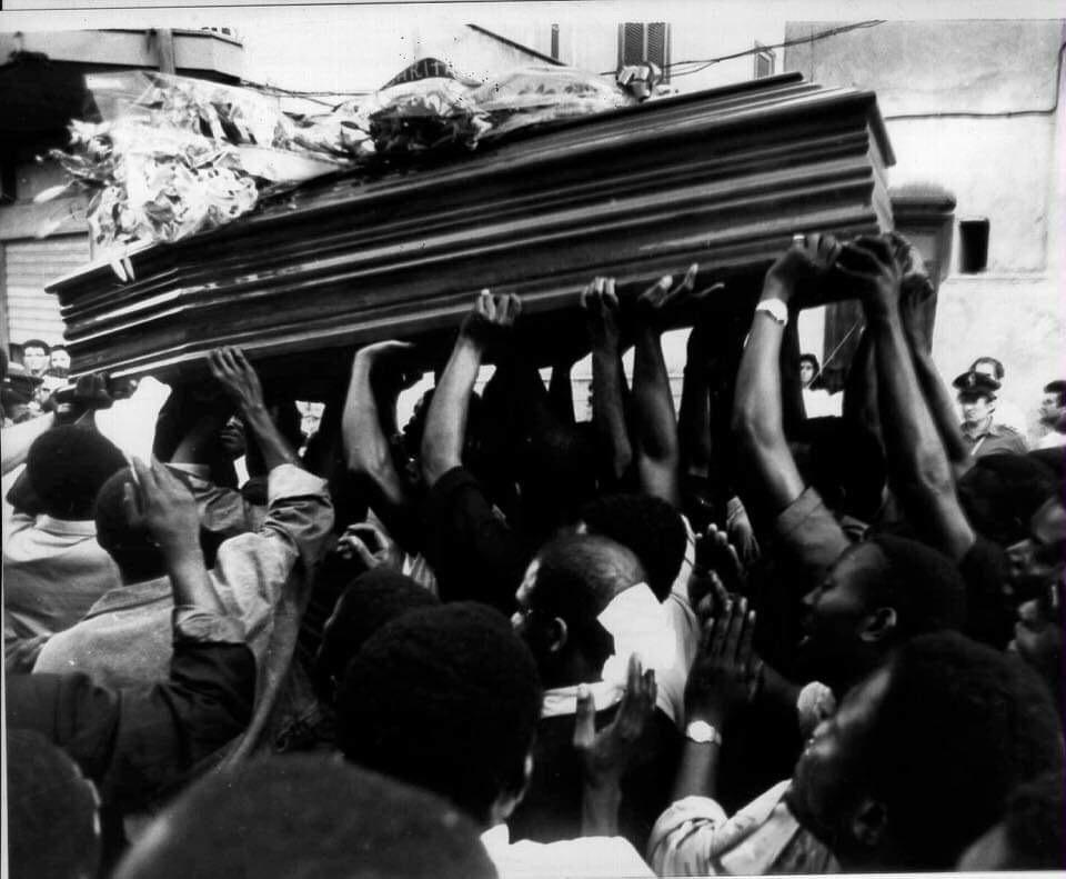 I migranti tengono il feretro di Jerry Masslo/ foto archivio Agenzia Frattari