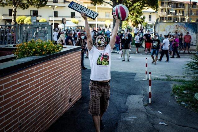 Manifestante di Mondragone innalza la targa di un'auto vandalizzata (di C. Benincasa)