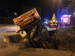 Il camion dei rifiuti finito nel torrente dopo aver sfondato un muretto.