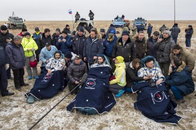 Da destra: Scott Kelly, Sergei Volkov e Mikhail Korniyenko, intenti a riposare, immediatamente dopo l'atterraggio avvenuto nei pressi della città di Dzhezkazgan, circondati dal personale di Terra.
