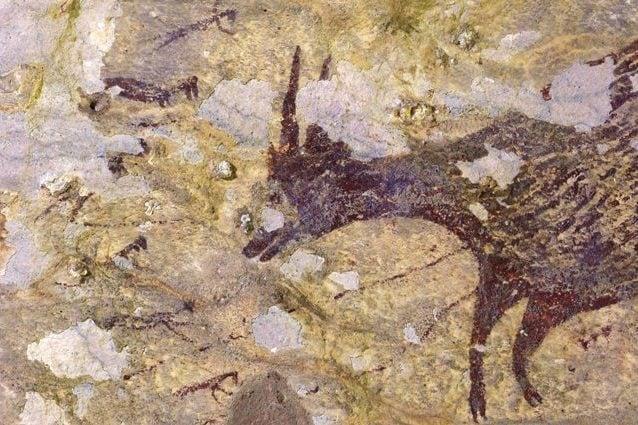 Pittura rupestre che mostra un anoa di pianura circondato da piccole figure antropomorfe. Credit: Adam Brumm / Ratno Sardi