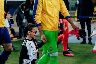 Il piccolo tifoso del Verona, malato, che accompagna le entrate in campo dei giocatori